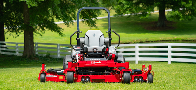 Exmark wide area mower on a fenced lawn